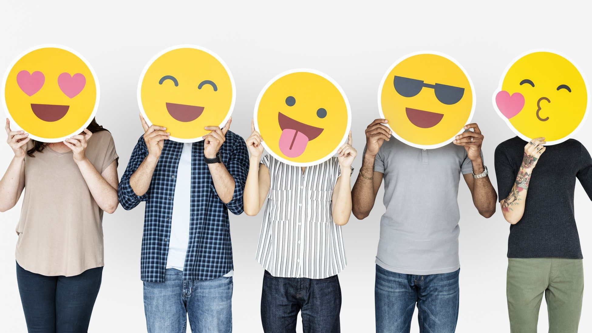 people holding emoji cutouts before their face